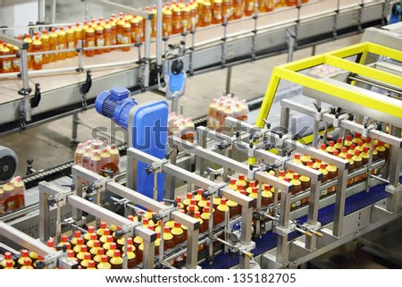Top view of three lines with bottles of beer with red caps in beer factory. - stock photo