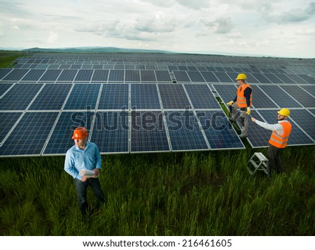 top view of three men wearing protection equipment inspecting solar panel station, outdoors - stock photo