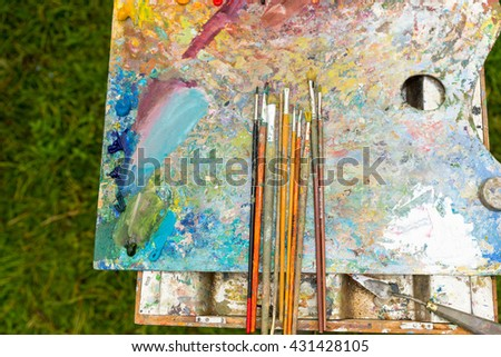 Top view of time-worn paintbrushes on an old colorful palette - stock photo
