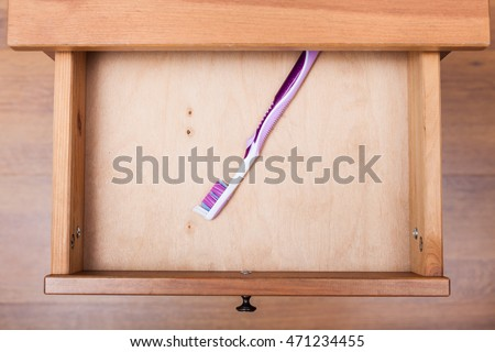 top view of toothbrush in open drawer of nightstand
