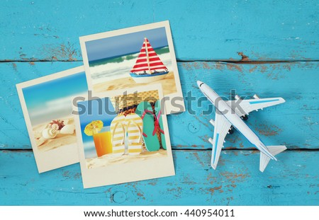Top view of travel instant photographs next to airplane over wooden table. traveling concept - stock photo
