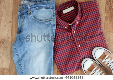Top view of traveler clothes isolated on wooden background - stock photo