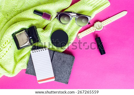 Top view of  trendy   spring  accessories  of modern woman on pink floor. Neon sweater , yellow wrist watch,glasses, lipstick, nail polish, perfume, electronic book and notepad. multicolor  mood.  - stock photo