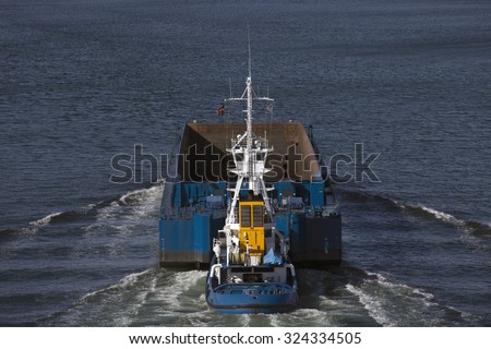 Top view of Tugboat pushing a heavy empty barge on the sea. Little Belt in Denmark. - stock photo