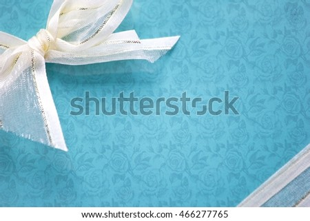 Top view of turquoise isolated gift box with white ribbon on white background
