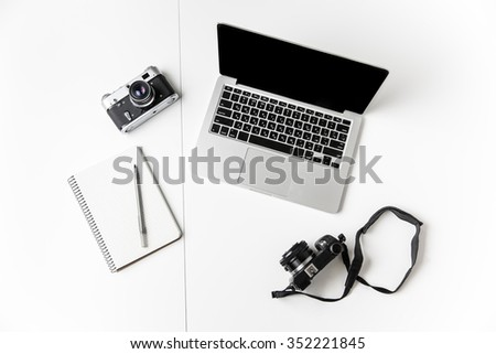 Top view of two cameras, notepad with pen and blank screen laptop isolated over white background - stock photo