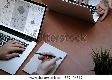 top view of two colleagues discussing data with new modern computer laptop with business strategy document and digital diagram as concept