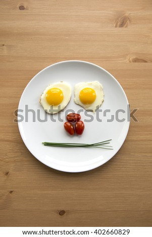 Top view of two fried eggs, tomatoes and chives forming a face on a white ceramic plate with copy space