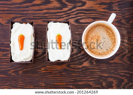 Top view of two homemade mini carrot cakes with mascarpone cream cheese icing and a cup of hot black coffee on a wooden tray
