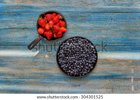 Top view of two iron plates, piled with fresh strawberries and blueberries - stock photo