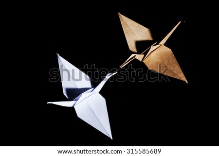 Top view of two origami cranes made from brown and white recycle paper on black background - stock photo