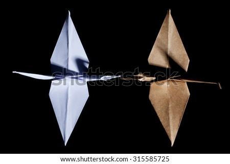 Top view of two origami cranes made from white and brown recycle paper on black background. - stock photo