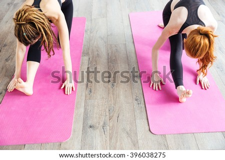 Top view of two slim young women stretching legs on pink yoga mat  - stock photo
