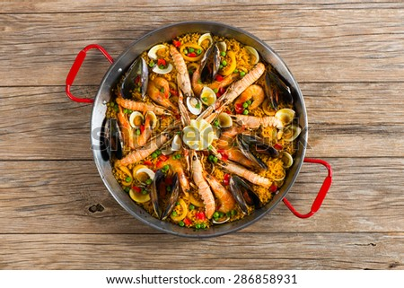 Top view of typical spanish seafood paella in traditional pan on a old wooden background - stock photo