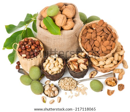 Top view of variety  nuts  (shelled and in their shells)  including almonds, cashew, hazelnuts, brazil nuts, peanuts, green walnuts with leaves and pine nuts.  Isolated on white background  - stock photo