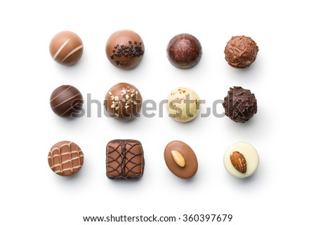 top view of various chocolate pralines on white background