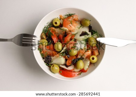 Top view of vegetarian salad in a white round plate on white background with soft shadows. Ingredients for healthy dieting: tomatoes, olives, kohlrabi, dill, basil, oil. Silverware is 'at the ready'. - stock photo