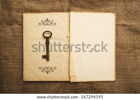 Top View of Vintage open book with old grunge paper textured pages and rusty key - stock photo