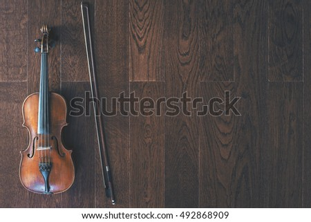 Top view of violin with bow on dark wooden floor with copy space