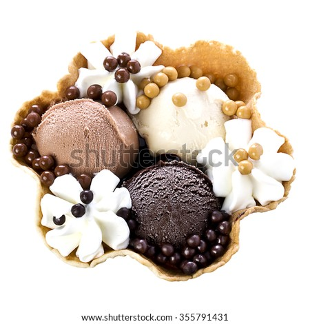 Top view of waffle bowl filled with ice cream with three different chocolate flavours: fondant, milky and white decorated with cream and pralines - stock photo