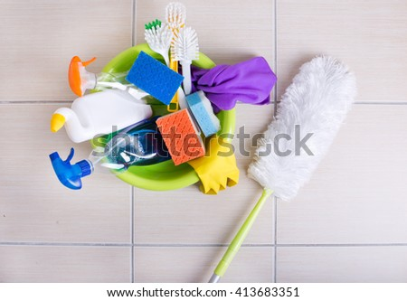 Top view of washbasin full of cleaning supplies and equipment on the ceramic tile floor - stock photo