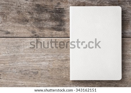 Top view of white book on old wooden plank background - stock photo