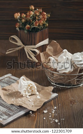 Top view of white broken meringue, metal vase with meringue and dry orange roses in a wooden square vase - stock photo