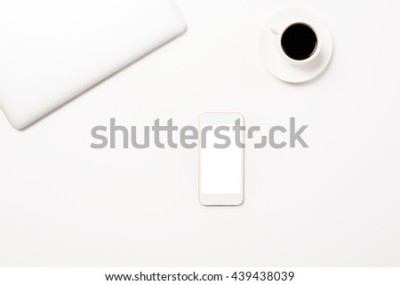 Top view of white desktop with closed laptop, coffee cup and blank smart phone. Mock up