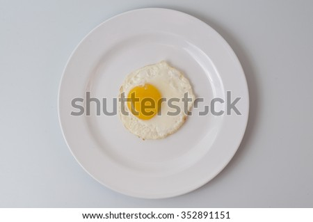 Top view of white dish with fried egg on white background. - stock photo