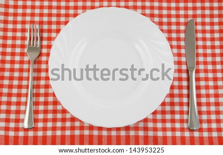 Top view of white plate, fork and knife on tablecloth