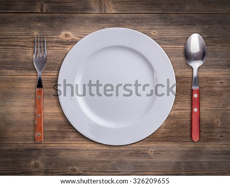 Top view of white plate with fork and spoon