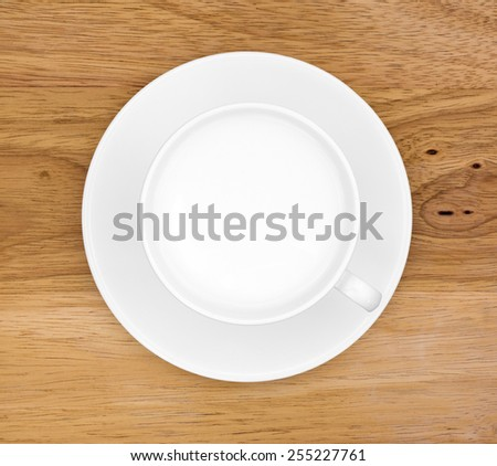 Top view of whole milk in a coffee cup and saucer on a wood table top. - stock photo