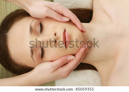 Top view of woman at  spa having  massage on her face