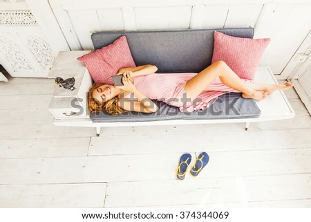 top view of woman lying on a couch and using phone - stock photo