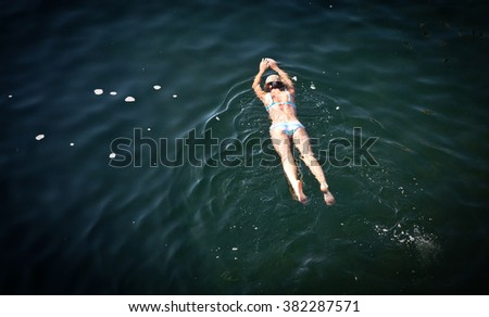 Top view of woman swimming in natural sea water pool