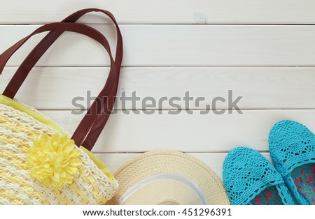 Top view of woman vacation fashion objects on white wooden background