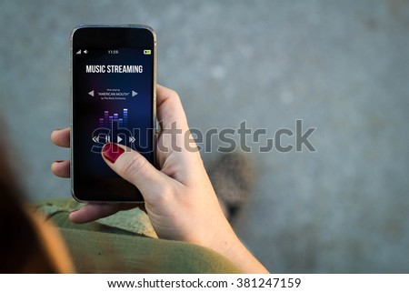 Top view of woman walking in the street using her mobile phone to listen music streaming with copy space. All screen graphics are made up. - stock photo