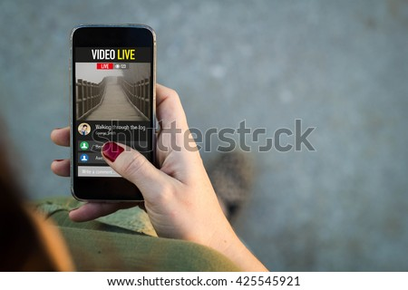 Top view of woman walking in the street using her mobile phone to watch a live video. All screen graphics are made up. - stock photo
