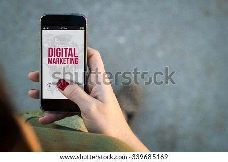 Top view of woman walking in the street using her mobile phone with digital marketing on screen. All screen graphics are made up. - stock photo