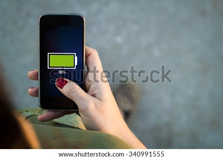 Top view of woman walking in the street using her mobile phone with full battery on screen with copyspace. All screen graphics are made up. - stock photo