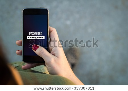 Top view of woman walking in the street using her mobile phone with password screen with copyspace. All screen graphics are made up. - stock photo