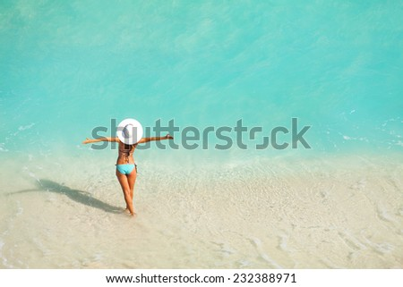 Top view of woman with white hat standing in ocean - stock photo