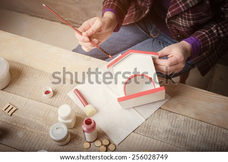 Top view of  women's hands during  handcrafting a decorative house - stock photo