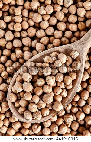 Top view of wood spoon full of chick peas beans. Chick-pea background. Nut is a main ingredient of hummus and many other vegan dishes. - stock photo