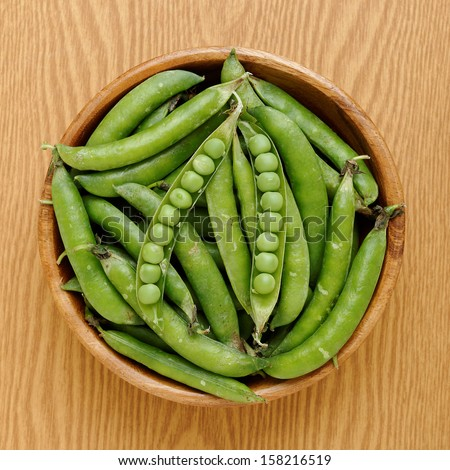 Top view of wooden bowl full of fresh peas - stock photo