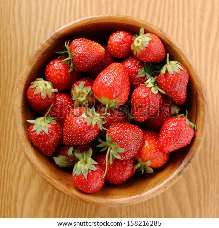 Top view of wooden bowl full of strawberries - stock photo