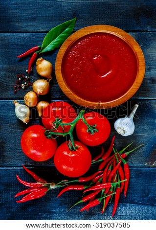 Top view of wooden bowl with tomato sauce and fresh ingredients on dark vintage background. Vegetarian food, health or cooking concept. - stock photo