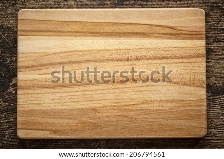top view of wooden cutting board on old wooden table - stock photo