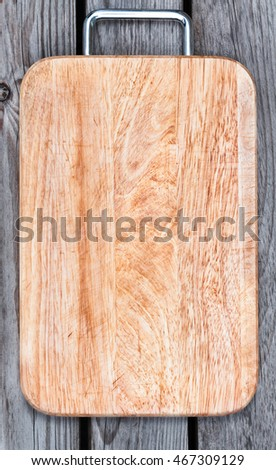 "Top view of wooden cutting board on old wooden table. There is an inscription ""menu""."