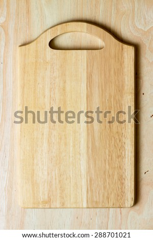 Top view of wooden cutting board on wooden table